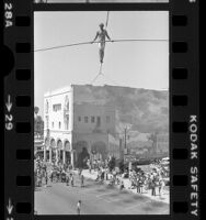 Steve McPeak walking tight rope across Windward Avenue in Venice, Calif., 1979