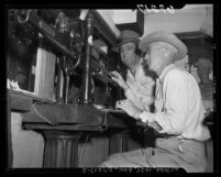 Two men working the scales at Los Angeles Union Stock Yards, 1950