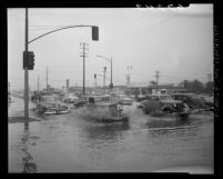 Automobiles driving through flooded intersection of Sepulveda Blvd. and Slauson Ave in Los Angeles, Calif., 1950