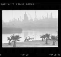 Lake scene in park with oil refinery in background in Harbor City, Calif., 1979