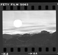 Sun setting behind housing developing on ridge near Mulholland Drive in Los Angeles, Calif., 1979
