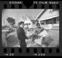 Police officer Jose Najera delivering Christmas package to Dennis Crump in Los Angeles, Calif., 1979