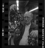 Engraver, Jack Zeider holding up string of bracelets honoring American hostages in Iran, Santa Monica, Calif.  1980