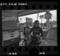 Woman getting gas at an ARCO ampm mini market in Los Angeles, Calif., 1980