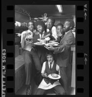 Los Angeles based music group, the BusBoys posing in a kitchen, 1980