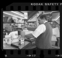 Ralph's Supermarket cashier, Mike Moore, demonstrating barcode scanner in Los Angeles, Calif., 1980