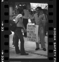 """Fusion Energy Foundation advocate, with sign reading """"Nuclear Plants Are Built Better Than Jane Fonda,"""" talking to traveler at Los Angeles International Airport, 1980"""