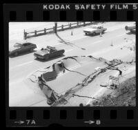 Automobiles driving around buckled pavement on Pacific Coast Highway near Las Tunas Beach, Calif., 1980