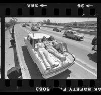 Three teenagers sunbathing on the hood of their stalled car on shoulder of Santa Monica Freeway, Los Angeles, 1980