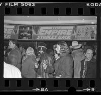 "People in theatre lobby decorated with ""Empire Strikes Back"" banner in Los Angeles, Calif., 1980"