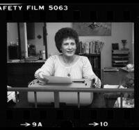 Nancy Ledins, transsexual and former Catholic priest, seated at her typewriter, Van Nuys, 1980