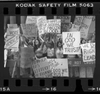 "Demonstrators with various anti-abortion and ""In God We Trust"" placards outside the 1980 Democratic National Convention in New York"