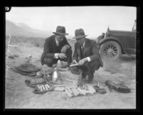 Two men examining kit of dynamite and wire found during sabotage incidents of Owens Valley Aqueduct, Calif., circa 1924