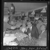 Governor Edmund G. (Pat) Brown tastes strawberry as he tours Los Angeles' Grand Central Market in 1962