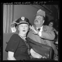 "Comedian Jackie Gleason placing conductors hat on reporter Hedda Hopper during train junket named ""The Great Gleason Express,"" in Los Angeles, Calif., 1962"