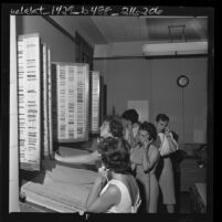 Five city hall receptionists taking telephone reservations for municipal golf courses tee times in Los Angeles, Calif., 1962