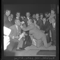 Kirk Douglas smearing cement on Ken Murray's face at Grauman's Chinese Theater, 1962