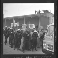 Police form cordon to hold back pickets at the Lockheed plant in Van Nuys, Calif., 1962
