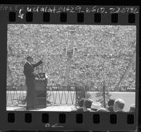 Evangelist Billy Graham speaking to crowd Los Angeles Memorial Coliseum, 1963
