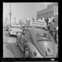 View looking past John Birch Society placard at demonstrators picketing Yugoslavia's President Tito's visit to Los Angeles, Calif., 1963