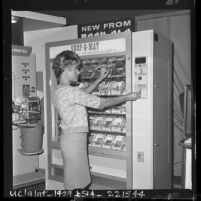 Louise Peden demonstrates coin operated vending machine at Automatic Merchandising show in Los Angeles, Calif., 1963