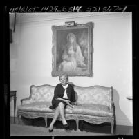 Actress Mary Pickford seated under a portrait of herself at the Pickfair Estate in Los Angeles, Calif., 1963
