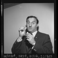1/2 length portrait of comedian Danny Thomas with pills he takes for his voice, 1963