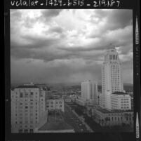 Cityscape of  Los Angeles City Hall, Federal and State buildings with dark cloud filled sky, 1963