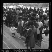 Children and adults with heads bowed in vigil for the four killed in Birmingham, Ala. bombing, Pasadena, Calif., 1963