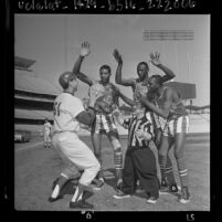 John Werhas shooting basketball as three Globetrotters play defense on infield of Dodgers Stadium, 1964