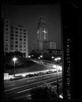 Night scene of Los Angeles City Hall with windows lit to form a cross in memorial to John F. Kennedy, Calif., 1963