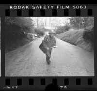 Mailman Jim Korkus walking up steepest street, Fargo Street, in Los Angeles, 1978