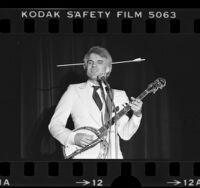 Steve Martin playing the banjo with arrow through head, 1978