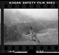Resident assisting with hose line during wildfire in Black Canyon, Calif., 1978