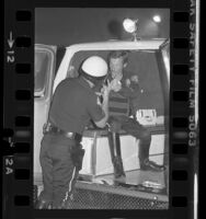 Los Angeles police officer and actor Kenneth Osmond talking with fellow officer in back of van, Los Angeles, Calif., 1980