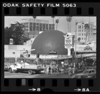 """Pickets with placards reading """"Save the Derby"""" in front of Brown Derby restaurant that's wrapped in scaffolding, Los Angeles, Calif., 1980"""