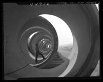 Worker standing inside section of 12-foot pipe of sewer line in Los Angeles, Calif., 1947