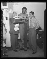 Boxing Inspector Bill Smith checks weight of Bantamweight Champion Harold Dade, Calif., 1947