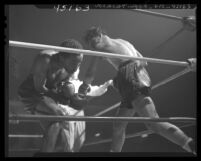 Boxer Manuel Ortiz throwing a right hand blow to Harold Dade in 1947 match, Los Angeles, Calif.