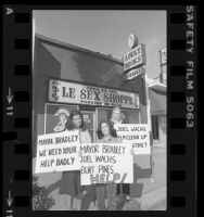 "Three women holding signs, one reading ""Joel Wachs Help Clean Up Our District,"" in front of 24-hour ""Le Sex Shoppe"" in Los Angeles, Calif., 1980"
