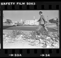 Man walking past lot covered with litter and weeds in Los Angeles, Calif., 1980