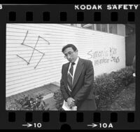 Rabbi Marvin Hier standing before anti-Semitic graffiti written on Simon Wiesenthal Center of Holocaust Studies in Los Angeles, Calif., 1981
