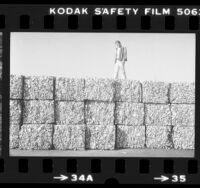 Errol Segal of Active Recycling Co. walking atop bales of aluminum cans in Los Angeles, Calif., 1984