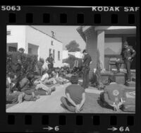 Police and 18 undocumented aliens with hands tied outside raided house in South Central Los Angeles, Calif., 1981