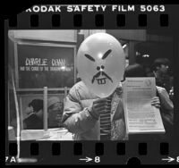 "Demonstrator holding up balloon with a stereotype Asian face at theatre showing a ""Charlie Chan "" movie in Los Angeles, Calif., 1981"