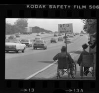 """Two men in wheelchair procession on Ventura Freeway with sign reading """"RTD is Unfair"""", Los Angeles, Calif., 1981"""