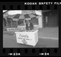 Carl Karcher, founder of Carl's Jr., standing at hot dog cart in front of Karcher headquarters in Anaheim, Calif., 1981