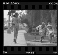 Man with walkman jogging past elderly couple seated on park bench in Santa Monica, Calif., 1981