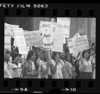 "UCLA students with signs, one reading ""Money for Minds not Bombs"" during Veteran's Day teach-in on nuclear weapons in Los Angeles, Calif., 1981"