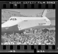 President Ronald Reagan on podium next to the space shuttle Enterprise as crowd cheers at Edwards Air Force Base, Calif., 1982